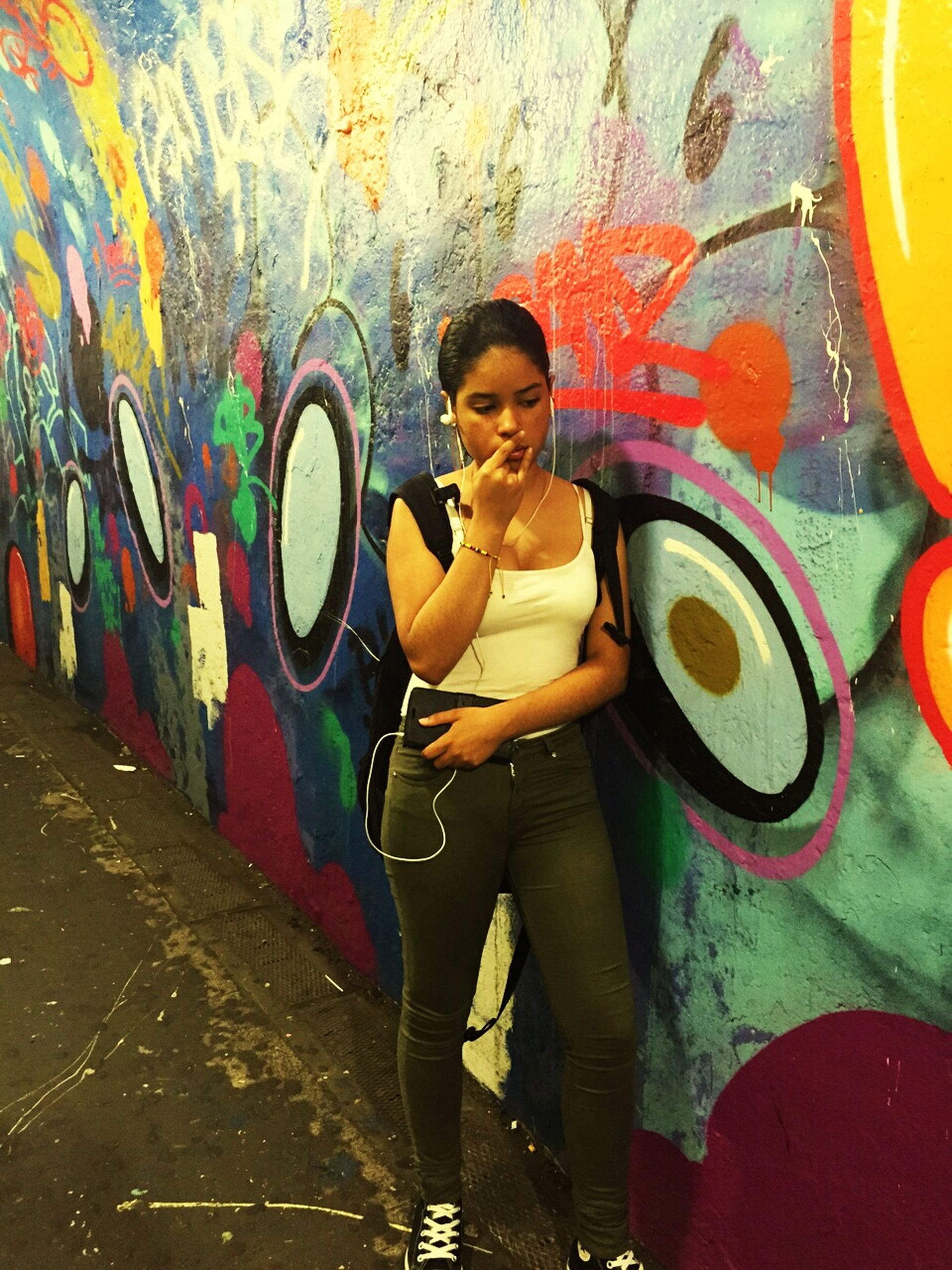 lifestyles, graffiti, young adult, leisure activity, casual clothing, looking at camera, person, portrait, front view, young women, happiness, standing, art, wall - building feature, creativity, smiling, full length