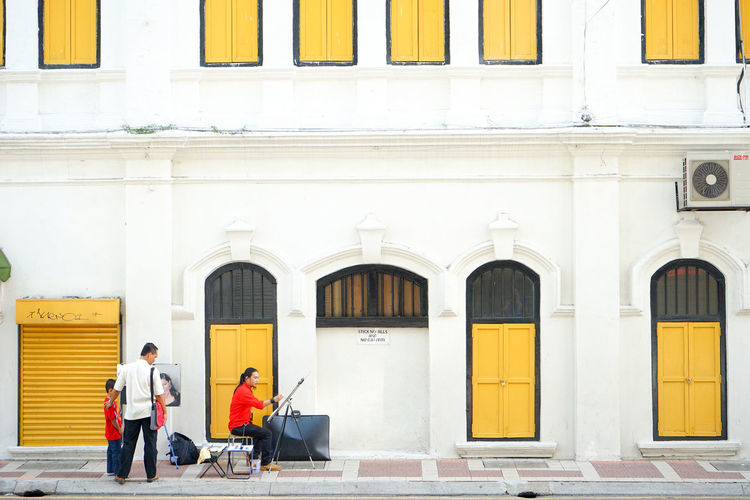 KUALA LUMPUR, MALAYSIA - April 12, 2015: Men artist painting on the street. A street artist in the old town. Image contain certain grain or noise and soft focus. Adult Adults Only Artist Painting Creative Day Draw People Street Artist Streetphotography
