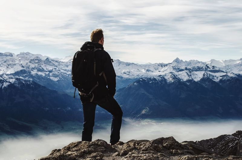 Rear view of man with backpack standing on rock against snowcapped mountains