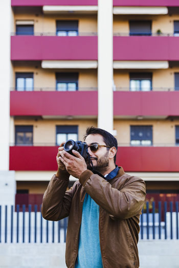 Man wearing sunglasses photographing with camera while standing against building