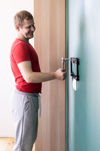 Side view of man standing against door at home