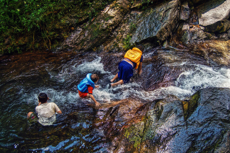 High angle view of children playing in river flowing over rock formations at forest