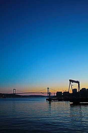 Water Sky Clear Sky Copy Space Blue Waterfront No People Transportation Nature Architecture Bridge Built Structure Bridge - Man Made Structure Sunset Silhouette Connection Sea Beauty In Nature Outdoors Construction Equipment