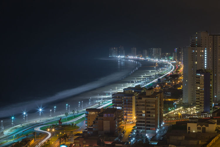High Angle View Of Buildings By Sea At Night