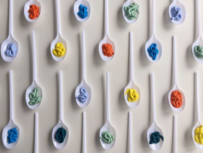Directly Above Shot Of Watercolor Paints In Spoons Arranged On Table