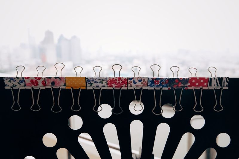 Close-up of paper clips against sky