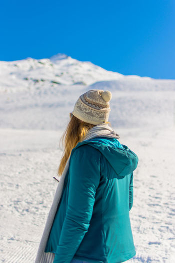 Woman in warm clothes while standing on snow covered land