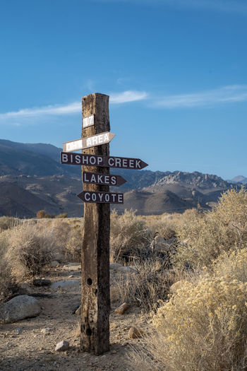 Wooden sign post  and arrows in eastern sierra nevada mountains  and desert landscape
