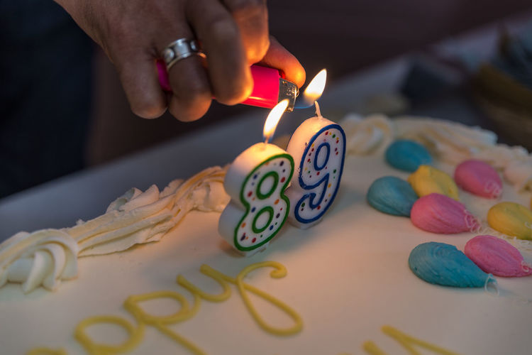 Human Hand Lighting Candle On Cake