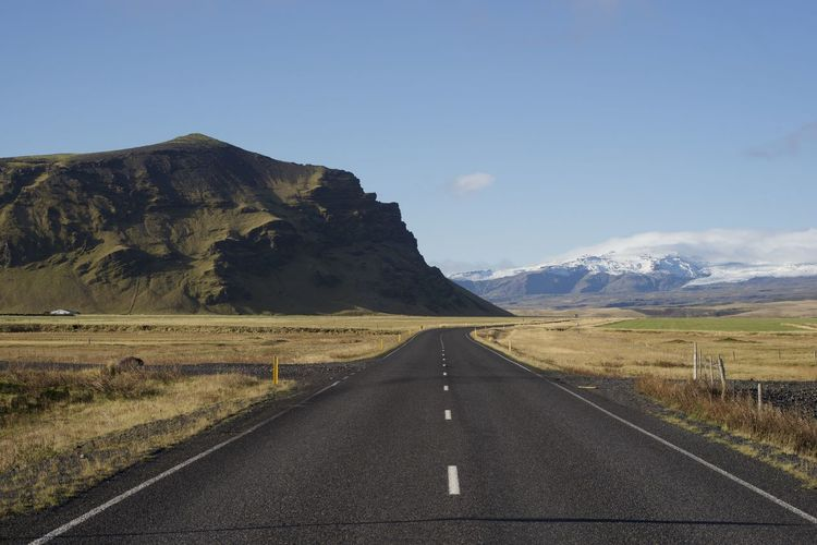 Lonely road leading towards the icelandic mountains