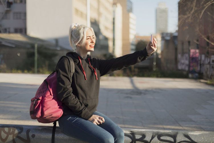 young beautiful woman sitting and taking a picture with mobile phone Adult Architecture Arms Raised Beautiful Woman Building Exterior Built Structure City Clothing Day Focus On Foreground Hair Hairstyle Human Arm Leisure Activity Lifestyles One Person Outdoors Real People Sitting Three Quarter Length Women Young Adult Young Women