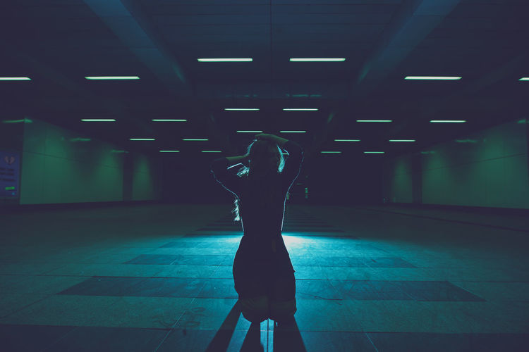 Young woman kneeling in underground walkway