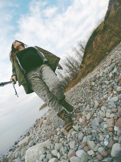 Low angle view of woman with monopod walking on stones against sky