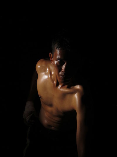 High Angle Portrait Of Sweaty Shirtless Man Standing Against Black Background
