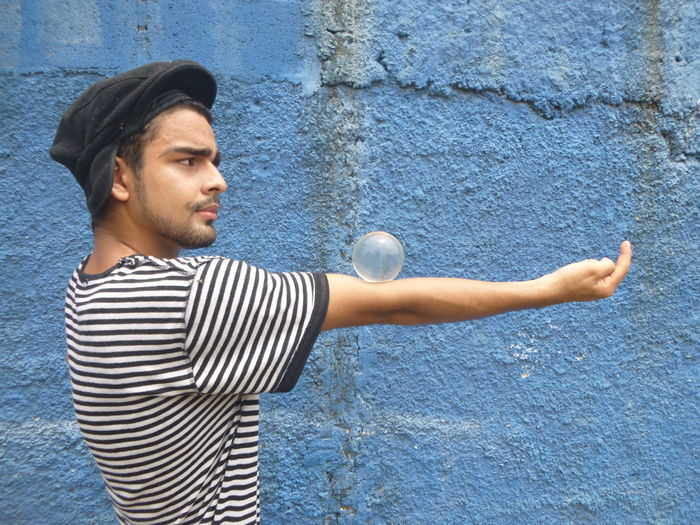 Man Balancing Ball On Hand By Wall