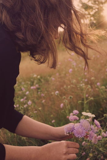 Picking flowers in the sunset Beauty In Nature Day Field Flower Freshness Girls Growth Leisure Activity Lifestyles Nature One Person Outdoors Picking Flowers  Plant Real People Side View Sunlight Sunlight Sunset Women Young Adult Young Women