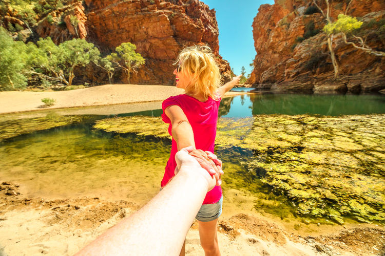 Woman holding hands of man while standing at riverbank