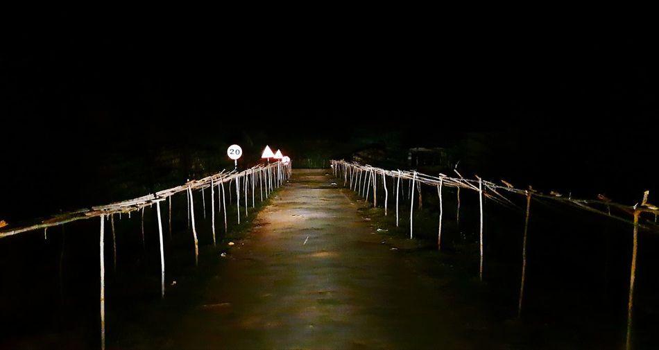 Illuminated road leading towards bridge against sky at night