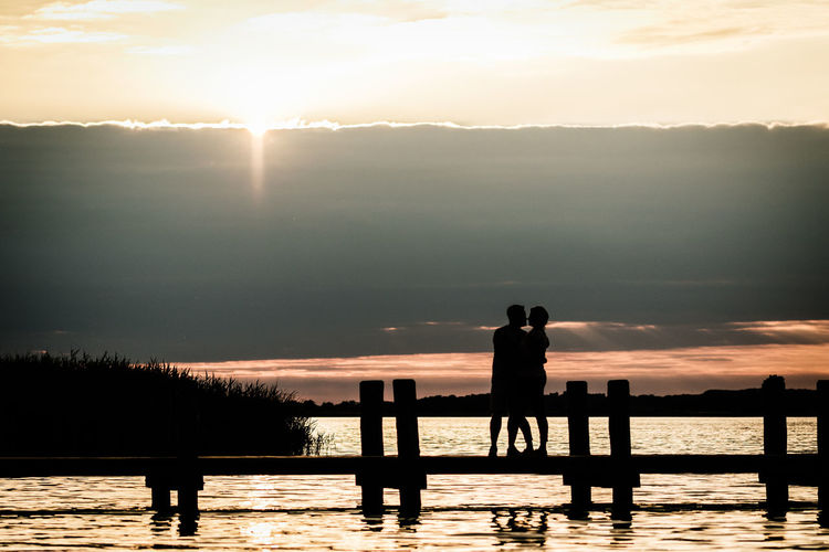 Two people kissing at landing stage next to lake during sunset Couple Love Romantic Beauty In Nature Idyllic Kissing Leisure Activity Lifestyles Looking At View Nature Outdoors Real People Roman Scenics - Nature Silhouette Sky Standing Sunlight Sunset Togetherness Tranquil Scene Tranquility Two People Water