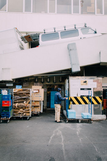 Man holding cart with boxes outside warehouse