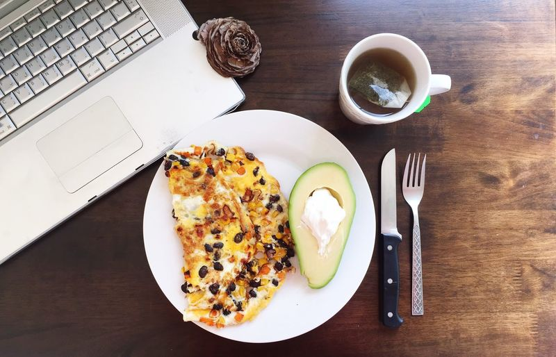 High Angle View Of Breakfast And Laptop On Table