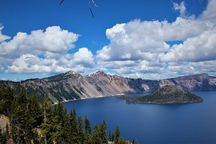 Scenic view of wizard island in the middle of crater lake in oregon with a beautiful,cloudy sky