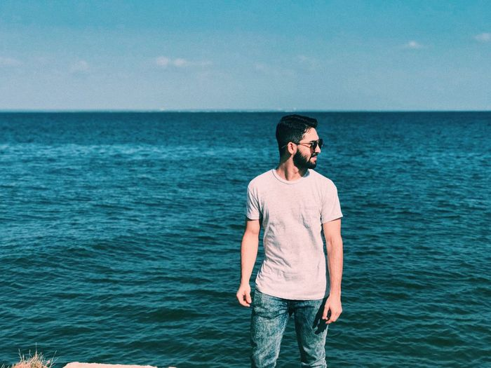 Man Standing Against Sea And Sky During Sunny Day