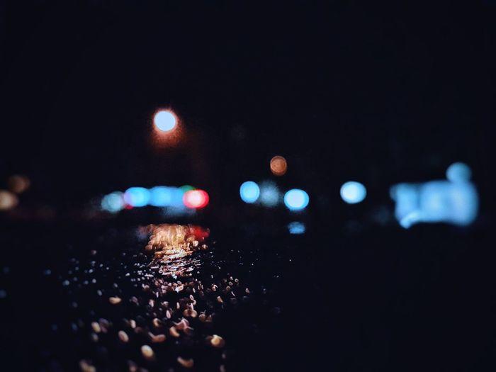 Defocused image of illuminated lights on road at night