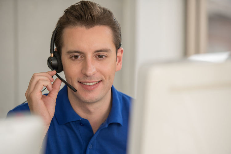 Male customer representative talking over headset in office