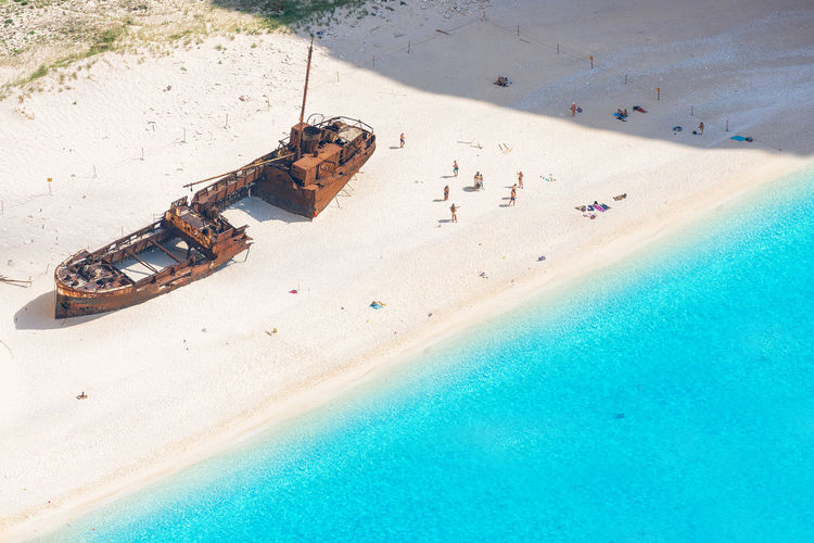 High angle view of shipwreck and people at beach