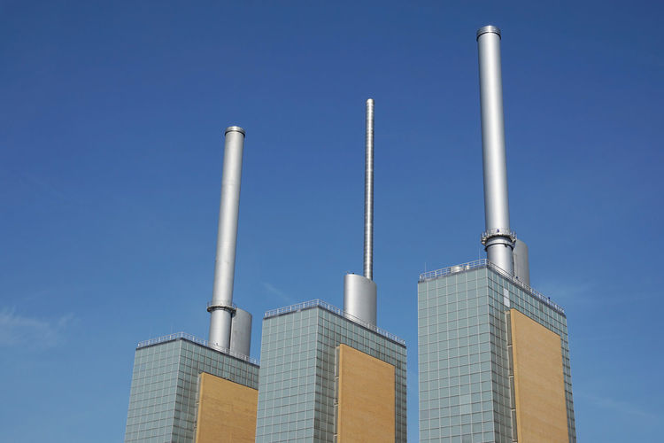 Low angle view of smoke stacks on factories against blue sky