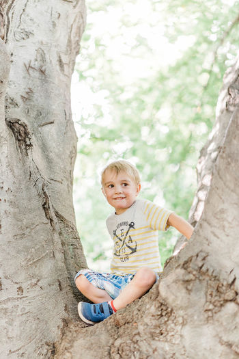 Portrait of smiling boy on tree trunk