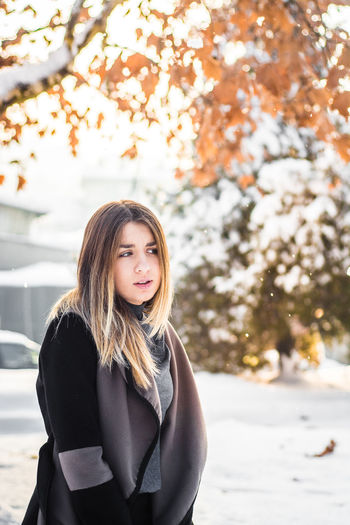 Portrait of beautiful young woman standing against tree during winter