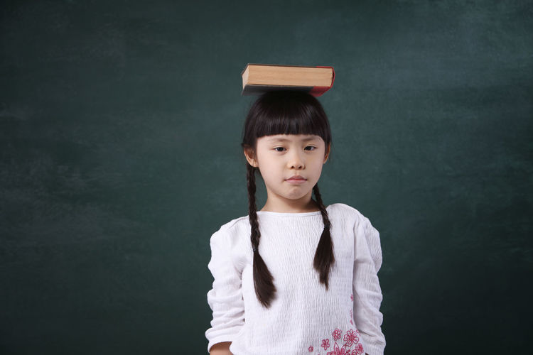 girl holding a book Asian  Happiness Mischief Student Adorable Back To School Balance Blackboard  Book Book On Head Chalkboard Cheerful Childhood Children Only Concept Cute Education Elementary Age Front View Girl Holding Knowledge One Person Portrait School