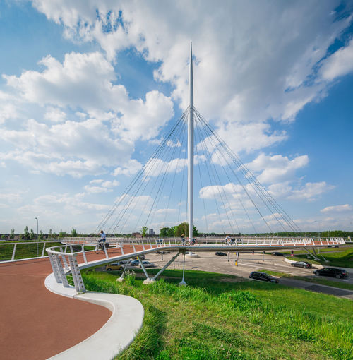 "The Hovenring is a suspended cycle path roundabout in the province of North Brabant in the Netherlands and the first of its kind in the world.[1] It is situated in between the localities of Eindhoven, Veldhoven and Meerhoven which accounts for its name, which is Dutch for ""Ring of the 'Hovens'"". Cable-stayed Bridge Cloud - Sky Cyclist Day Modern Architecture Outdoors Roundabout Trafic"