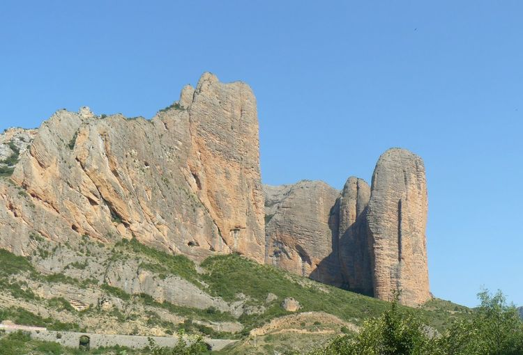 Ancient Civilization Beauty In Nature Blue Clear Sky Day Eroded Formation Land Low Angle View Mayos De Riglos Mountain Mountain Range Nature No People Outdoors Plant Rock Rock - Object Rock Formation Scenics - Nature Sky Solid Tranquil Scene Tranquility Travel Destinations
