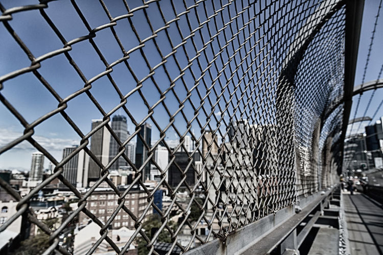 Close-up of chainlink fence in city