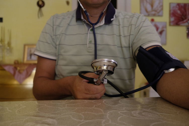 Midsection Of Doctor Holding Stethoscope In Office