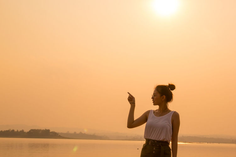 Woman pointing while standing against sea and sky during sunset