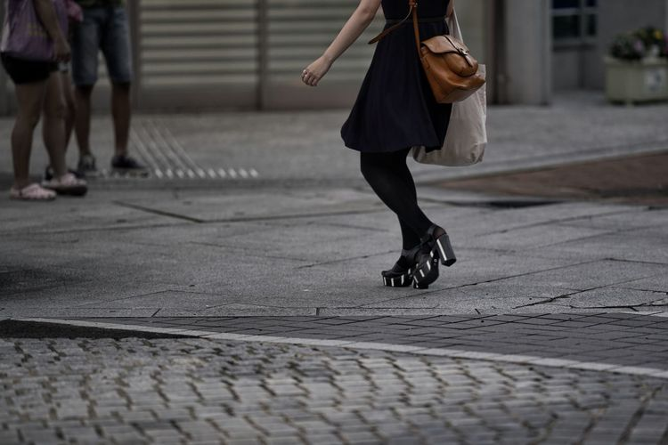 Low section of woman walking in city