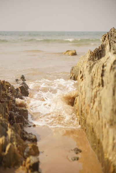Sea Splashes between the Rocks at the Beach