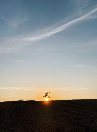 Silhouette airplane flying over field against sky during sunset