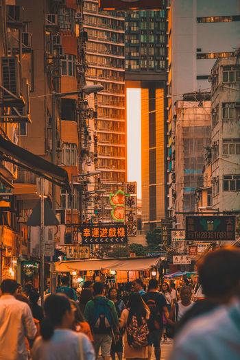People on street against buildings in city