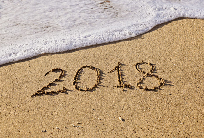 Concept on wet sand handwritten text 2018 and sea wave 2018 New Year Slim To Do List Annual Report Beach Close-up Conceptual Day Expectation Handwriting  Hope\ Message Nature New Beginings No People Outdoors Plans Sand Sea Single Word Start Summer Text Vacations Shades Of Winter