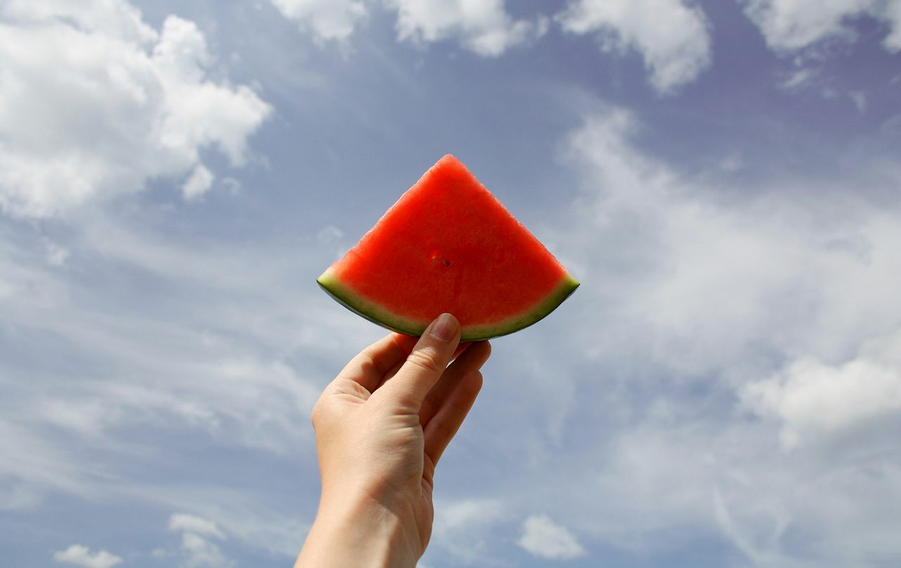Cropped hand holding watermelon slice against cloudy sky on sunny day