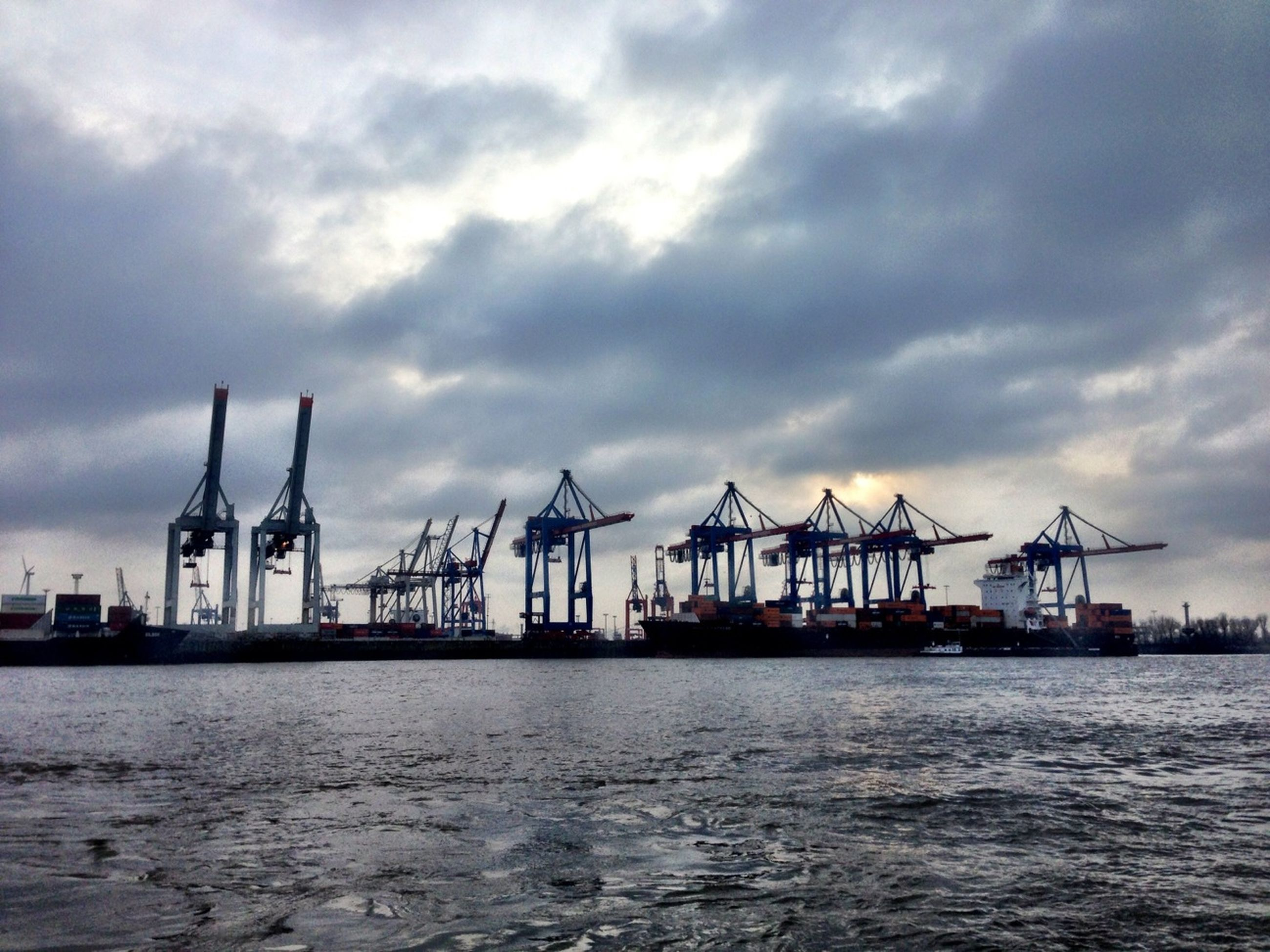water, waterfront, sky, sea, built structure, nautical vessel, architecture, cloud - sky, transportation, commercial dock, harbor, cloudy, building exterior, mode of transport, ship, crane - construction machinery, industry, freight transportation, cloud, shipping