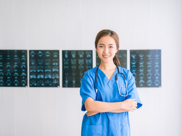 Portrait Of Female Doctor Smiling While Standing Against X-Rays On Wall
