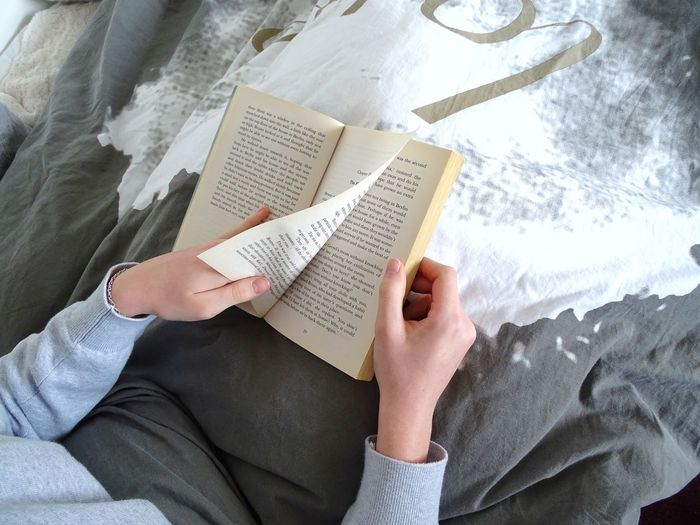 Midsection of woman reading book while sitting on bed at home