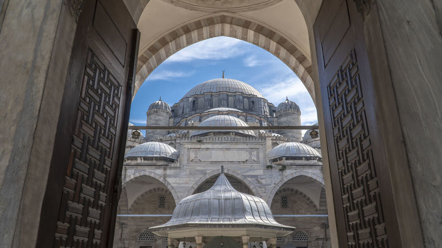 The Fatih Mosque (Conqueror's Mosque) in Fatih district, Istanbul, Turkey. A beautiful view from entrance gate. Entryway Civilization Carving - Craft Product Marble Historic Façade Calligraphy Architectural Feature Sky Built Structure Architecture Arch Place Of Worship Dome Islamic Architecture Religious  Ottoman Architecture Istanbul Turkey Historical Mosque Fatih Mosque Entrance Gate Islamic Religious Architecture Art And Craft Belief Ottoman Empire Carving Design Islamic Art Cultural Heritage Domestic Animals Fatih Camii Courtyard  Old Door Light And Shadow Sunlight Blue Sky And Clouds History Travel No People Outdoors Tourism Low Angle View Religion Travel Destinations Building Building Exterior Day