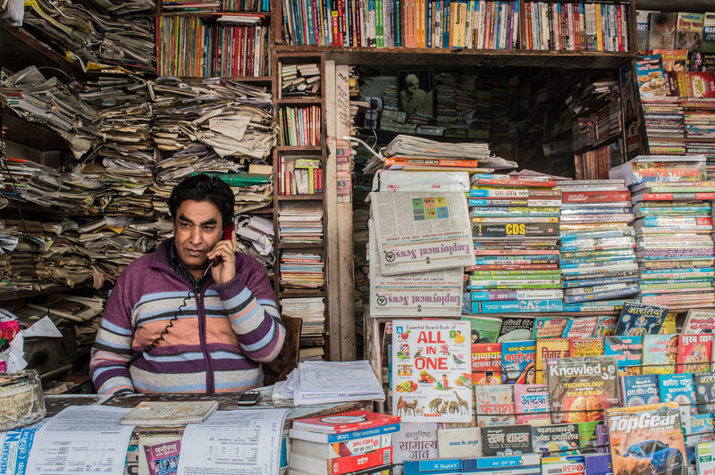 Abundance Adult Book Bookshelf Business Front View Indoors  Large Group Of Objects Lifestyles Looking At Camera Market One Person Portrait Publication Real People Retail  Shelf Smiling Stack Waist Up